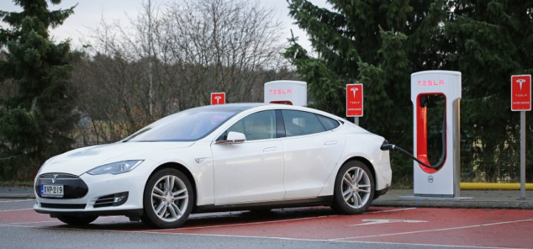 Paimio, Finland - November 15, 2015: White Tesla Model S electric car being charged at the Paimio Tesla Supercharger station. The Supercharger gives the Model S 270 km of range in about 30 minutes.